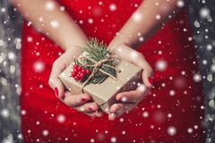 Weibliche Hände, die Weihnachtsgeschenkbox mit Niederlassung des Tannenbaums, glänzender Weihnachtshintergrund halten Lizenzfreie Stockbilder
