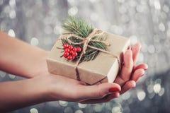 Weibliche Hände, die Weihnachtsgeschenkbox mit Niederlassung des Tannenbaums, glänzender Weihnachtshintergrund halten Lizenzfreies Stockbild