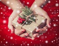 Weibliche Hände, die Weihnachtsgeschenkbox mit Niederlassung des Tannenbaums halten Stockbilder