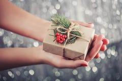 Weibliche Hände, die Weihnachtsgeschenkbox mit Niederlassung des Tannenbaums halten, Stockfotografie
