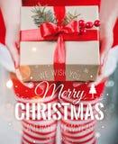 Weibliche Hände, die Weihnachtsgeschenkbox mit rotem Band und fröhlichen dem Weihnachten-und neuemjahr typografisch auf glänzende stockfotos
