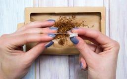 Weibliche Hände, die Zigarren mit Tabak rollen Lizenzfreies Stockbild