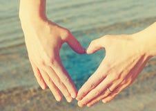 Weibliche Hände in Form von Herzen gegen das Meer Stockbild
