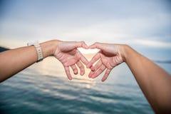 Weibliche Hände in Form von Herzen gegen den Himmel führen Sonnenstrahlen Lizenzfreies Stockbild