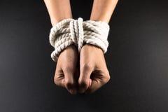 Weibliche Hände gesprungen in Knechtschaft mit Seil stockfotografie
