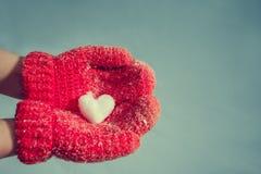 Weibliche Hände in gestrickten Handschuhen mit einem romantischen Rot der Weinlese hören Stockfotos