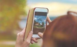 Weibliche Hände halten den Smartphone beim Schießen einer Landschaft in N Stockfoto