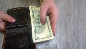 Weibliche Hände halten Dollarscheine von ihrem Geldbeutel und setzen sie zurück in den Geldbeutel stockfoto