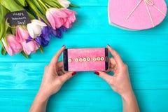 Weibliche Hände halten ein Telefon mit einer Mitteilung der Liebe Valentinstaghintergrund mit Blumenstrauß von Tulpen und von Ges lizenzfreies stockbild