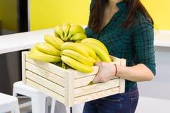 Weibliche Hände halten eine Holzkiste mit Bananen in der Küche Banane auf hölzernem Korb Stockfotografie