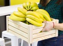 Weibliche Hände halten eine Holzkiste mit Bananen in der Küche Banane auf hölzernem Korb Lizenzfreies Stockbild