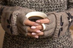 Weibliche Hände halten eine Kaffeetasse Stockfotografie