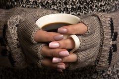 Weibliche Hände halten eine Kaffeetasse Lizenzfreie Stockfotografie