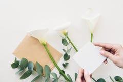 Weibliche Hände halten leeres weißes Blatt auf Hintergrund von Blumen Beschneidungspfad eingeschlossen Spott oben Stockfoto