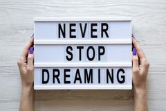 Weibliche Hände halten modernes Brett mit Text 'aufhören nie, über weißem hölzernem Hintergrund zu träumen ', oben Draufsicht, vo stockfotografie