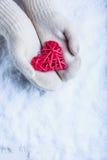 Weibliche Hände im Weiß strickten Handschuhe mit entwirrtem romantischem rotem Herzen der Weinlese auf Schneehintergrund Liebe un Lizenzfreie Stockfotografie