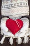 Weibliche Hände im Weiß strickten Handschuhe mit romantischem rotem Herzen Lizenzfreie Stockfotos