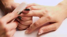 Weibliche Hände liegen auf einander und zeigen eine schöne handgemachte Kunstmaniküre auf einem hellen Gewebehintergrund Inneres stock video footage