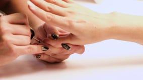 Weibliche Hände liegen auf einander und zeigen eine schöne handgemachte Kunstmaniküre auf einem hellen Gewebehintergrund Inneres stock video