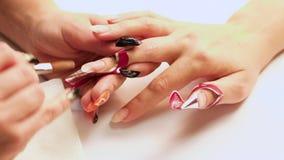 Weibliche Hände liegen auf einander und zeigen eine schöne handgemachte Kunstmaniküre auf einem hellen Gewebehintergrund Inneres stock footage