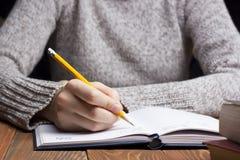Weibliche Hände mit Bleistiftschreiben auf Notizbuch Lizenzfreies Stockfoto