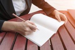 Weibliche Hände mit Bleistiftschreiben auf Notizbuch Stockbild