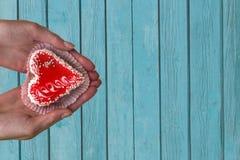 Weibliche Hände mit einem geformten Kuchen des Herzens auf einem Hintergrund einer alten hölzernen Beschaffenheit lizenzfreies stockbild