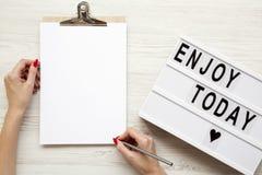 Weibliche Hände mit einem leeren noticepad und einem ` genießen heute ` Wort auf lightbox über weißem hölzernem Hintergrund, Drau stockbild