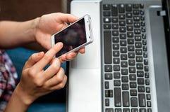Weibliche Hände mit Handy und Laptop lizenzfreies stockbild