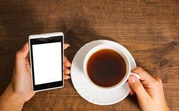 Weibliche Hände mit Handy und Tasse Tee auf hölzernem Hintergrund Stockfotografie