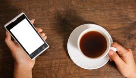 Weibliche Hände mit Handy und Tasse Tee auf hölzernem Hintergrund Stockfoto