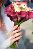 Weibliche Hände mit Hochzeitsblumenstrauß Lizenzfreies Stockbild