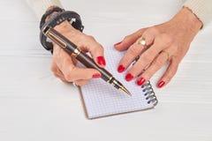 Weibliche Hände mit Luxusstift und Notizbuch Lizenzfreies Stockbild
