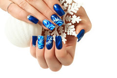 Weibliche Hände mit neuem Jahr entwerfen auf den Nägeln, die Schneeflocke halten Stockfoto