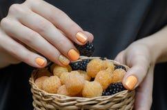 Weibliche Hände mit orange Nageldesign stockbild