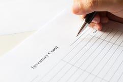 Weibliche Hände mit Stiftschreiben auf Inventarzählungsform lizenzfreie stockfotografie