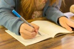 Weibliche Hände mit Stiftschreiben auf Notizbuch Lizenzfreies Stockfoto