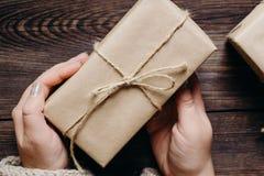Weibliche Hände mit verzierter Weihnachtsgeschenkbox stockbild