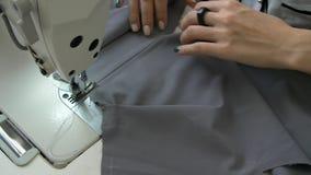 Weibliche Hände nähen ein graues Gewebe auf einer Nähmaschine stock video