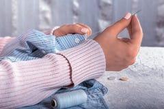 Weibliche Hände nähen einen Knopf stockfotografie