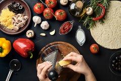 Weibliche Hände rieben den Käse, der auf Pizza, Bestandteile für das Kochen der Pizza auf schwarzer Tabelle, Draufsicht zerrieben lizenzfreies stockbild