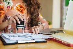 Weibliche Hände setzten einen Stempel auf Dokumente lizenzfreie stockfotos