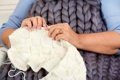 Weibliche Hände stricken eine Decke mit Stricknadeln liebhaberei lizenzfreie stockbilder