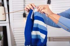 Weibliche Hände stricken eine Strickjacke mit Stricknadeln liebhaberei stockfoto