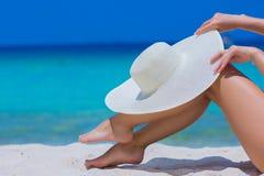 Weibliche Hände und Füße mit weißem Hut auf dem Strand Stockfotografie