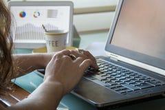 Weibliche Hände unter Verwendung des Laptops und der Tablette auf dem Innenministeriumdesktop Stockfotografie