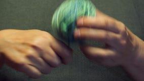 Weibliche Hände wickeln einen Ball des Garns unter warmem elektrischem Licht stock video footage