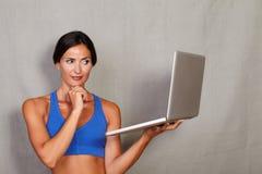 Weibliche haltene Laptop-Computer des erwachsenen langen Haares Stockfoto