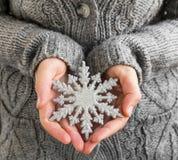 Weibliche haltene Weihnachtsschneeflocken-Dekoration Stockbild