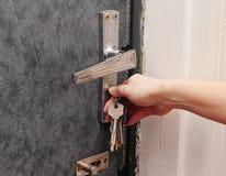 Weibliche Hand öffnet die Tür mit einem Schlüssel Stockfoto